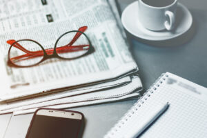 Desktop, office worker. News newspaper, glasses, notepad, modern mobile phone.