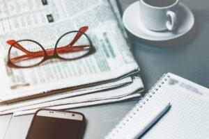 Desktop, office worker. News newspaper, glasses, notepad, modern mobile phone.