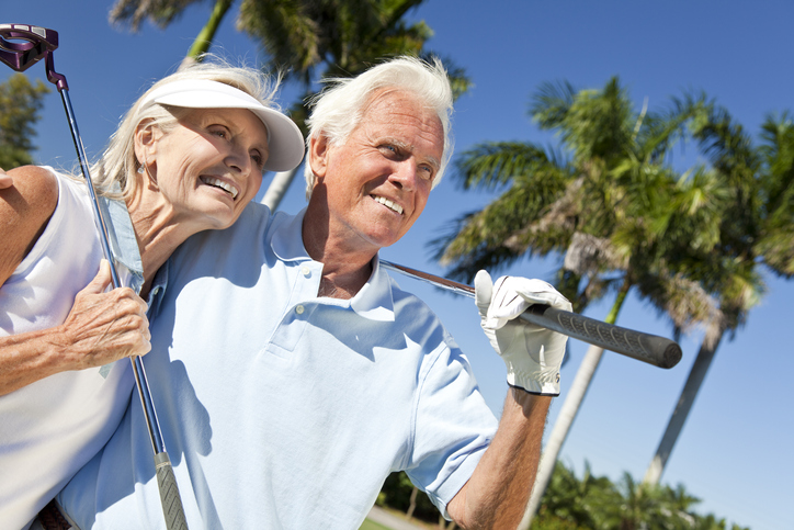 Happy senior couple playing golf with palms in background