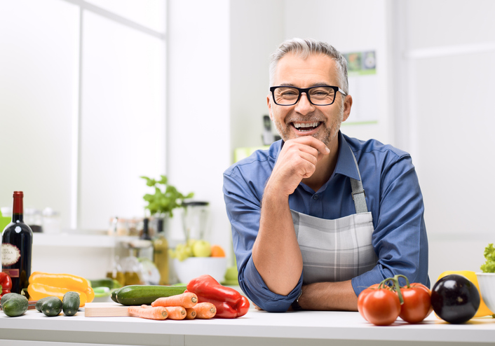 Confident smiling man posing in his kitchen