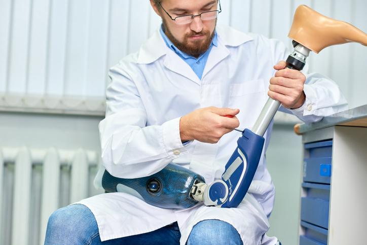 Bearded Doctor Assembling Prosthetic Leg