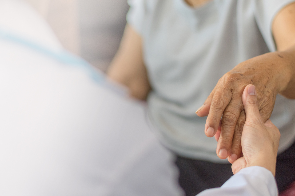 Parkinson and alzheimer female senior elderly patient with physician doctor exam in hospice care room.