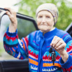 Senior woman holding car key and smiling