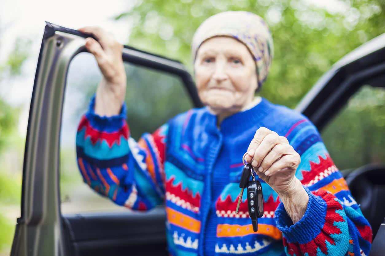 Senior woman holding car key and smiling