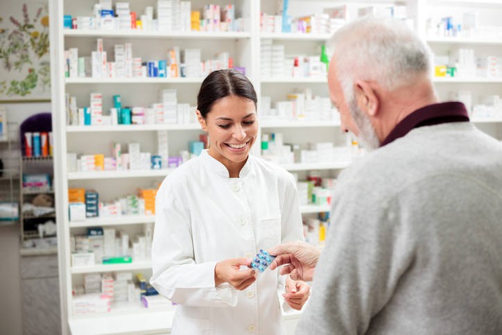 Female pharmacist giving medications to senior customer