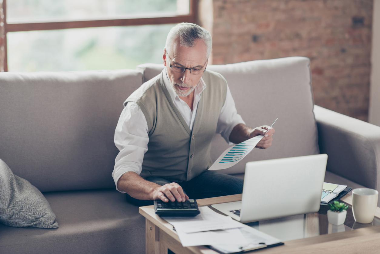 Old confident clever concentrated bearded grandpa is checking his calculations sitting in front of monitor at office