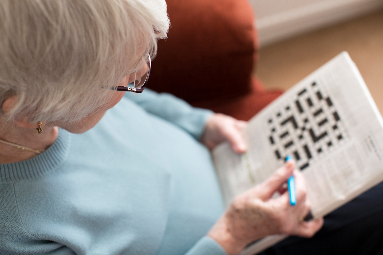 Senior Woman Doing Crossword Puzzle At Home