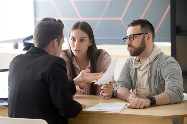 Angry millennial couple complaining about bad contract disputing with lawyer