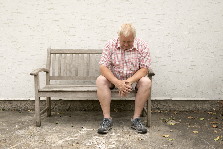 Worried mature man sitting on a wooden bench