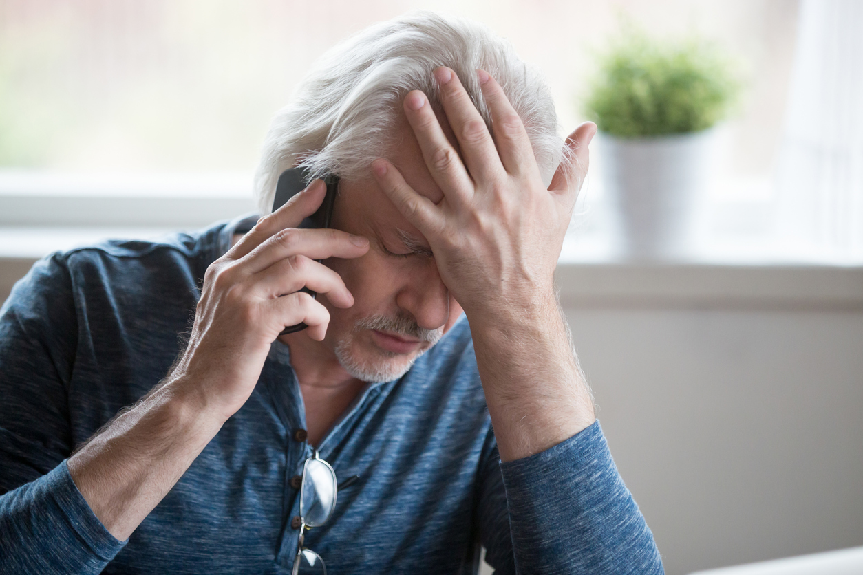 Frustrated mature man feeling upset desperate talking on the phone