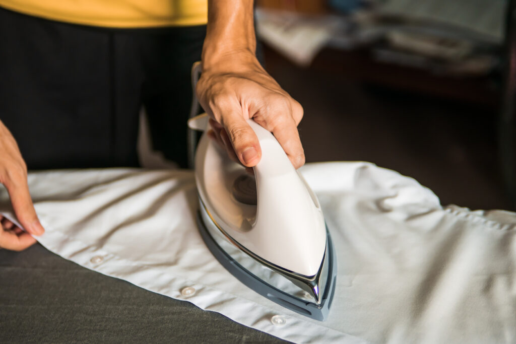 Men hand ironing white shirt on ironing board