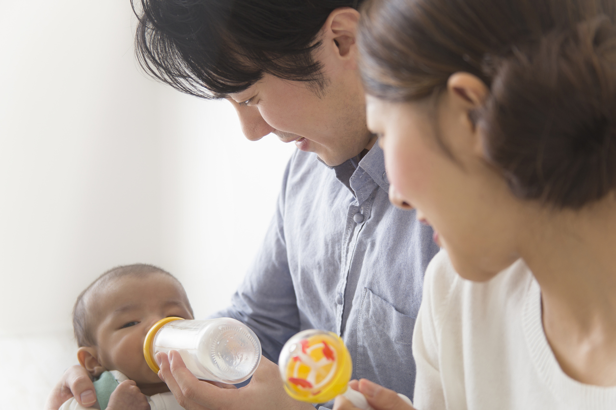 Japanese couple feeding baby milk from a bottle