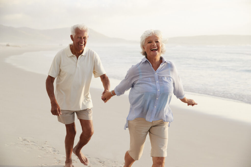 Senior Retired Couple Running Along Beach Hand In Hand Together