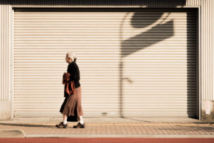 Aging population social issue of a widow lonely woman walking along the street of Japan