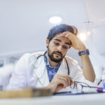 Stressed male doctor sat at his desk