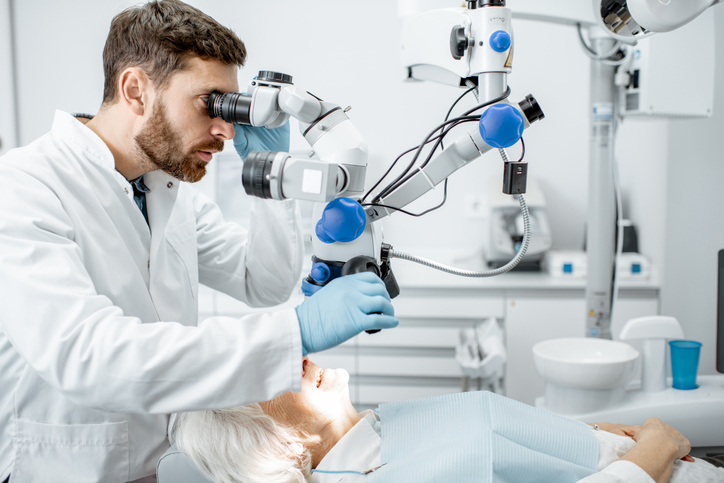 Dentist examining patient's teeth with a microscope