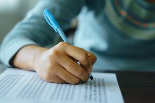 College student write on exam paper