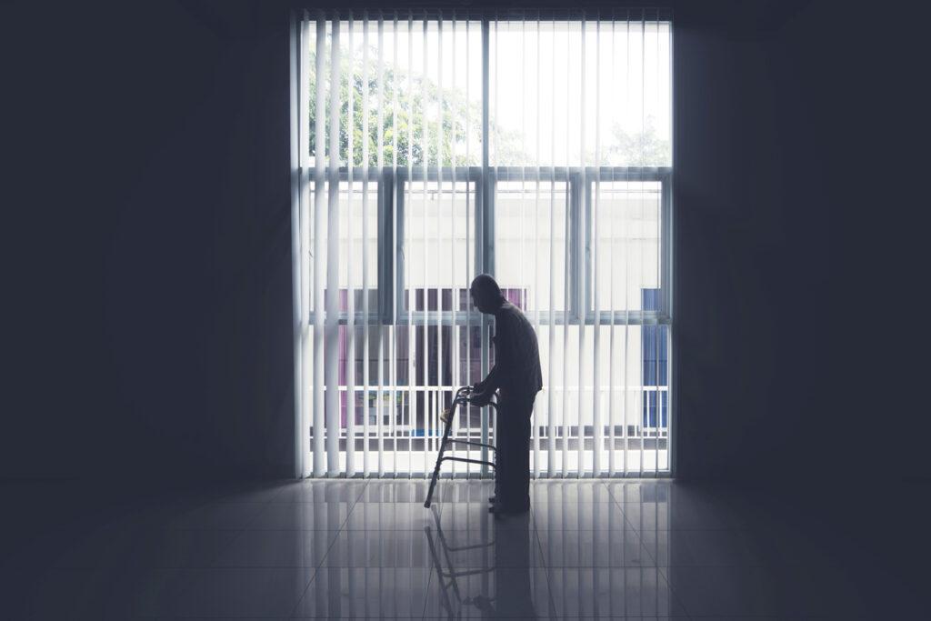 Old man walks near the window with a walker