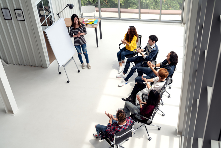 Young asian businesswoman explain idea to group of creative diverse team at modern office. Wide top view of manager standing against multiethnic people. Audience applauding speaker after presentation.