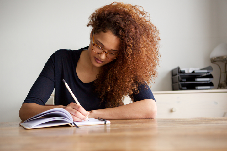 university student writing in book at home