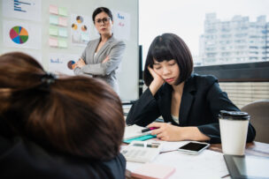 manager mad at businesswomen sleeping in meeting