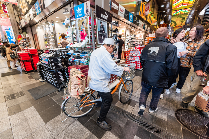Nishiki market street with chef in uniform man riding bicycle delivering bag of rice