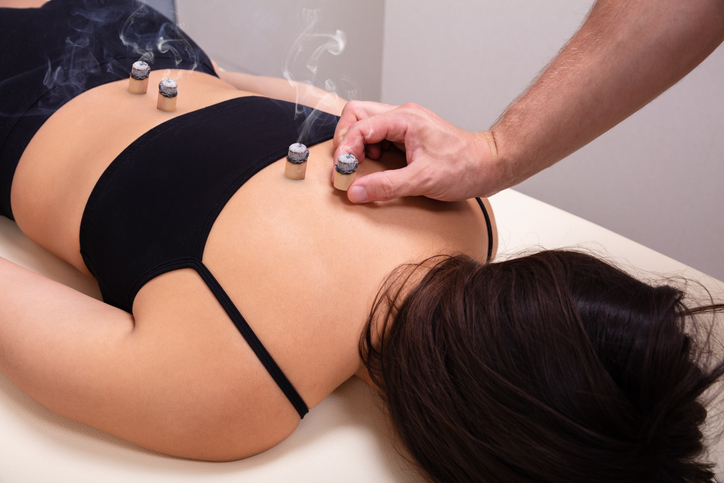 Woman Undergoing Therapy Using Moxa Stick