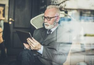 Senior businessman working on digital tablet at cafe.