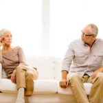 senior couple sitting on sofa at home