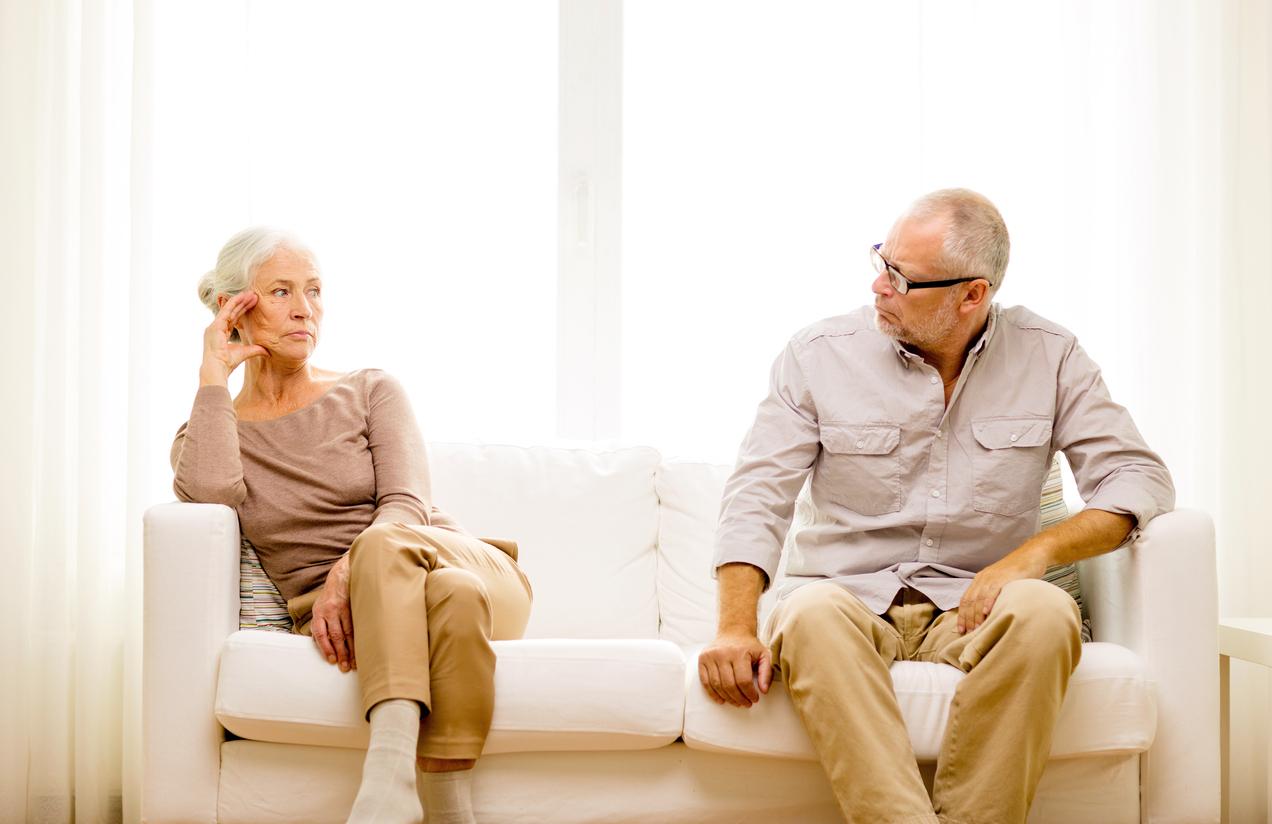 senior couple sitting on sofa at home