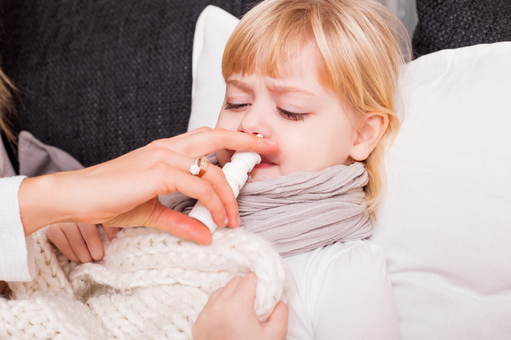 Child using medicine to treat cold