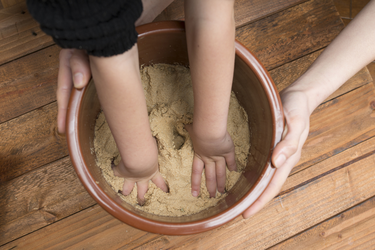 Parent and child hand mixing rice bran pickles