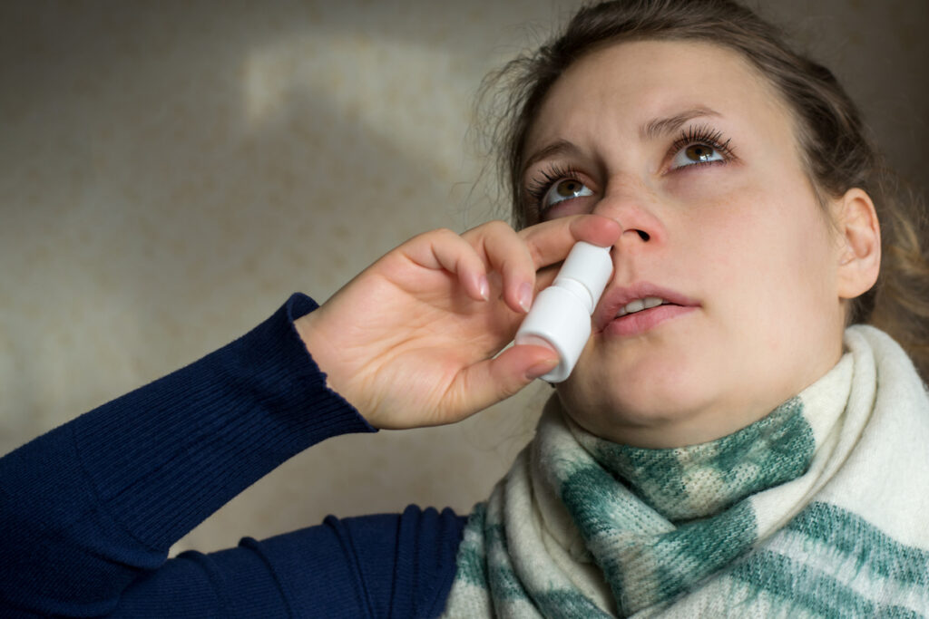 Sick girl sprays the spray from runny nose into the nasal pass