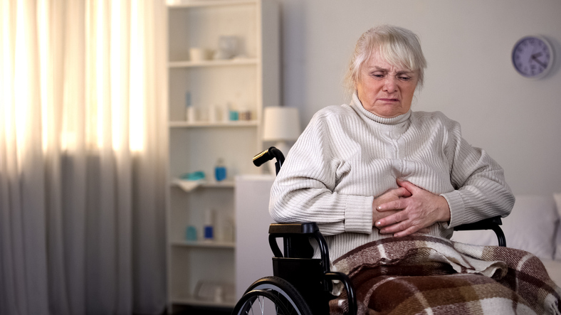 Handicapped old woman suffering from abdominal pain, health care, gastritis