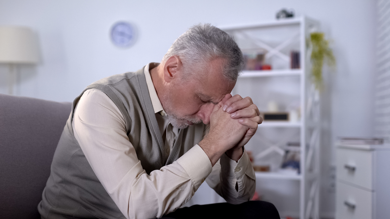 Elderly man sadly bowed head, feeling lonely and depressed, old age crisis