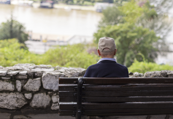 A lonely old man sitting on a bench in a park, looking at river