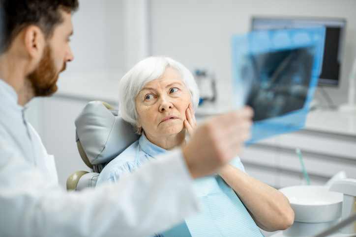 Dentist showing x-ray to the elder woman in the dentall office