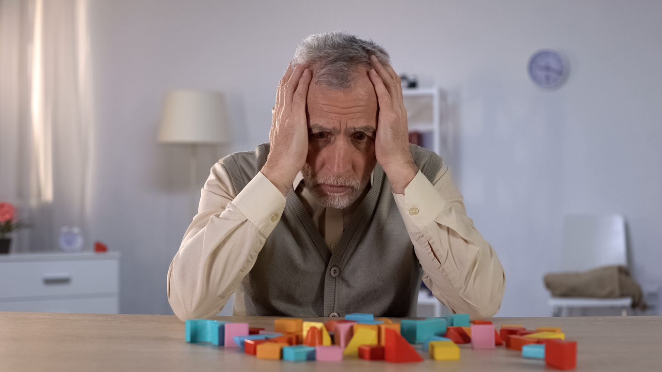 Pensive elderly man looking at color building blocks on table, old age dementia