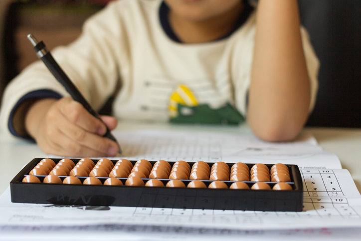 Boy counts with abacus in school.
