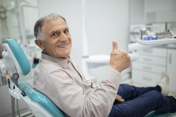 Old senior man sitting in a dental chair