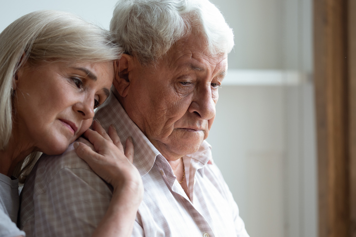 Middle-aged daughter snuggle to elderly father sharing his sorrows