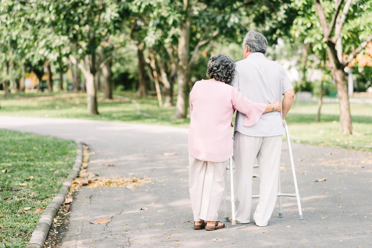 Senior couple talking a walk with walker
