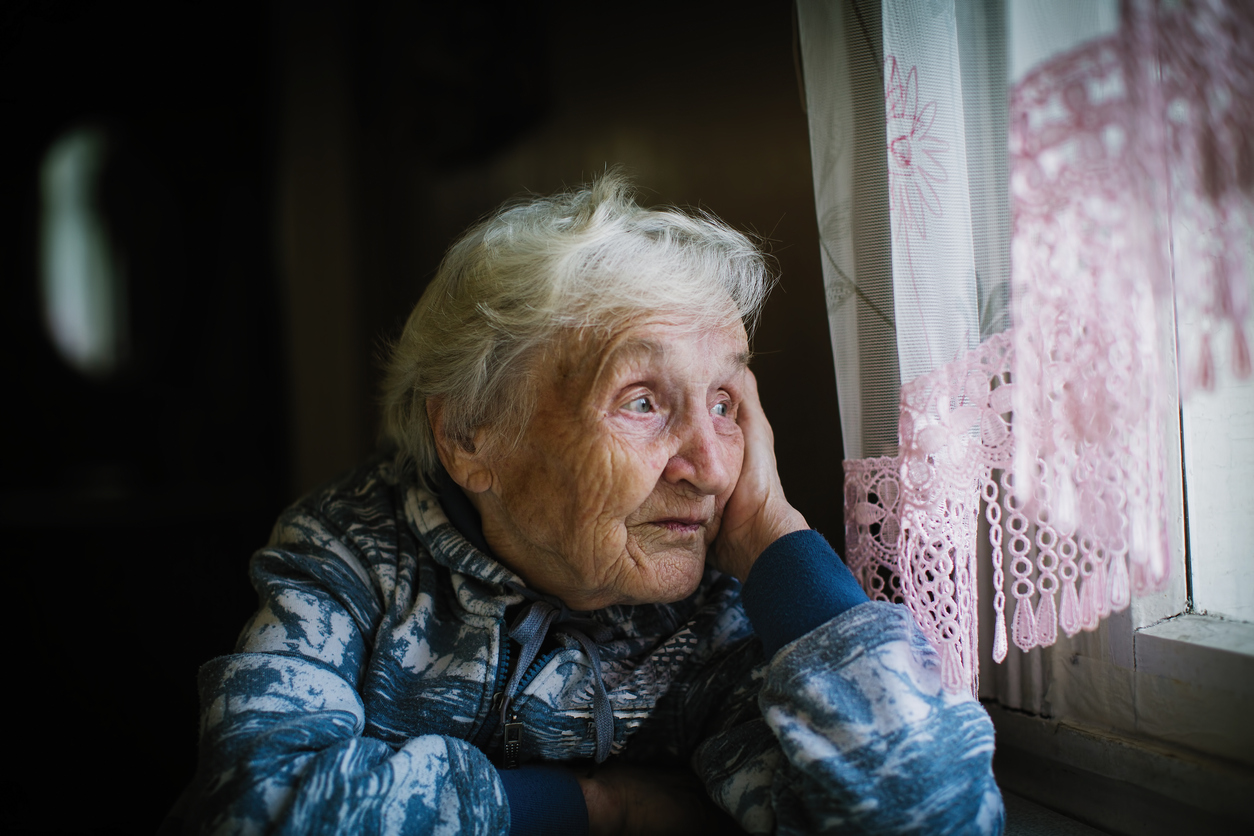 Elderly woman in the house sitting at the table looking out the window.