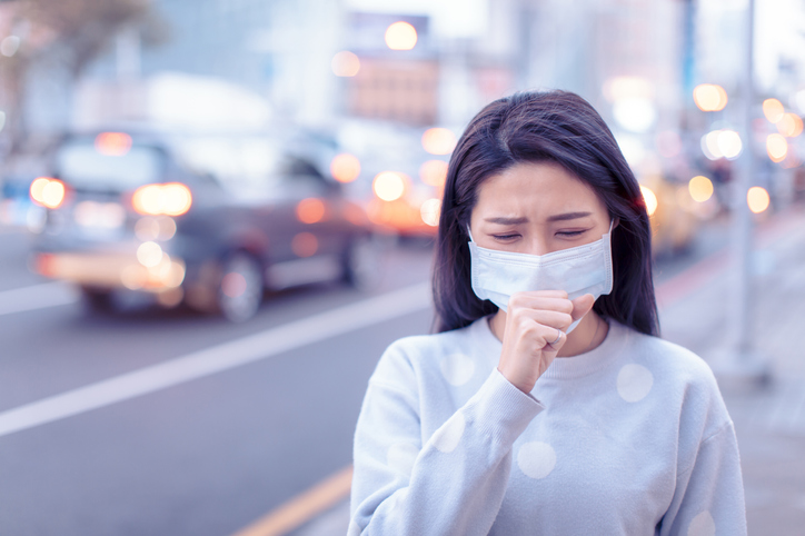 young woman wear mask in the city during Smog day