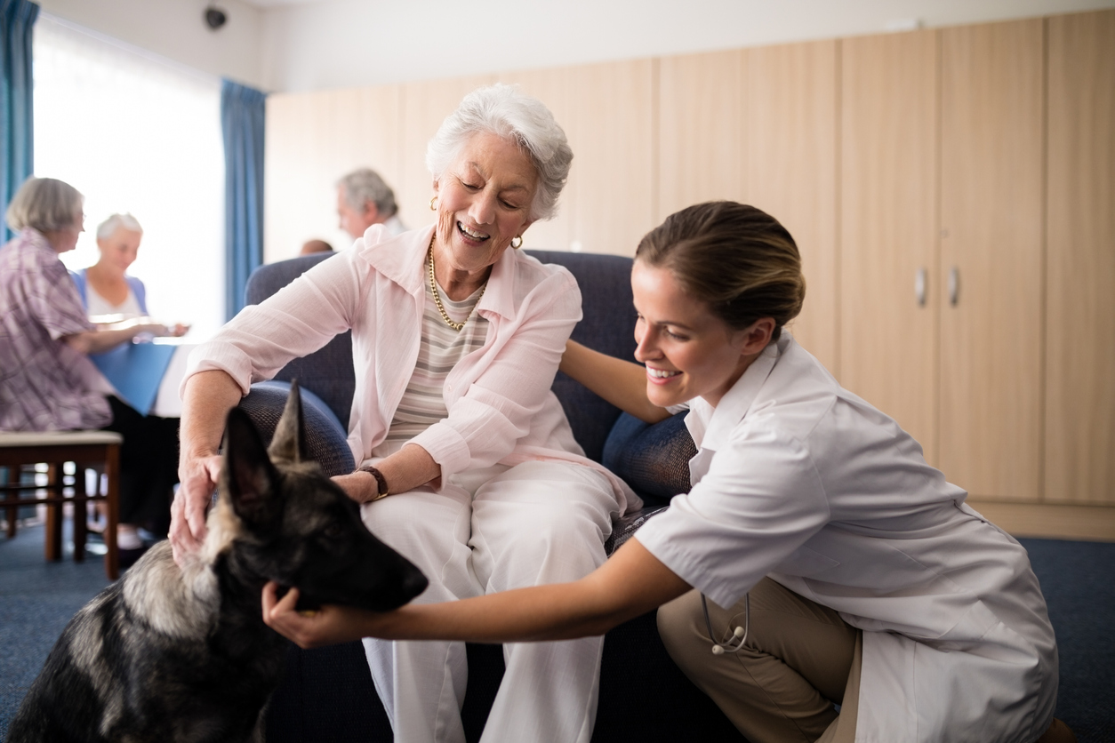 Portrait of smiling female doctor kneeling by senior woman stroking puppy