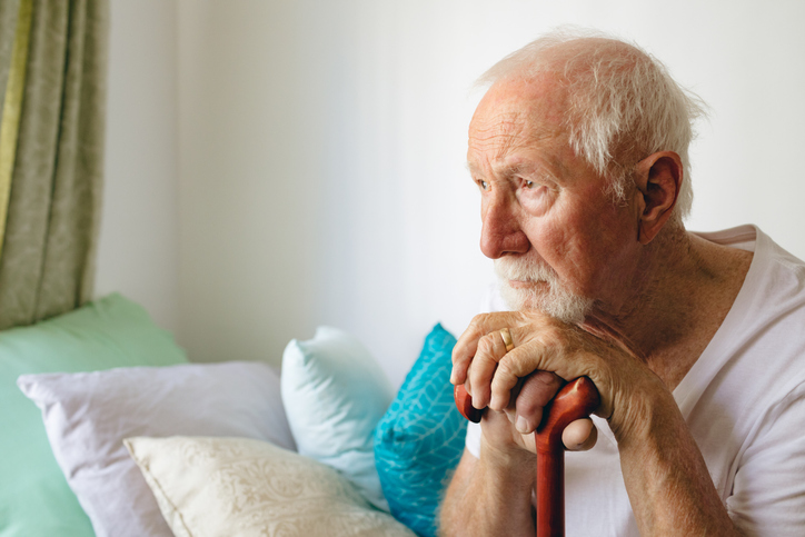 Senior male patient sitting upset on bed with stick at retirement home