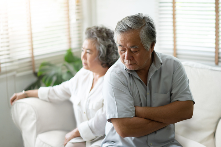 Upset Senior man sitting on sofa against the background of his wife.