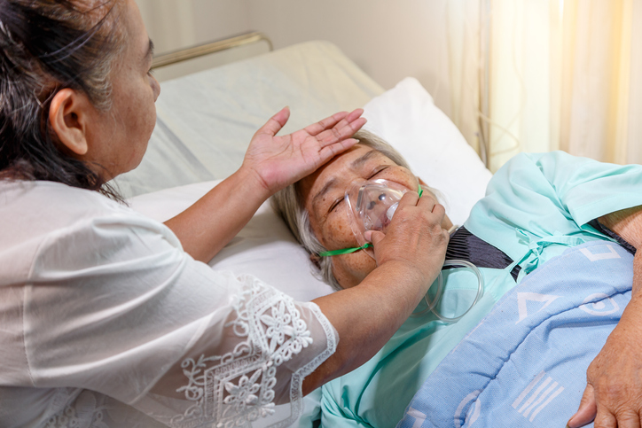 Asian daughter visiting her mother lying in bed at hospital room