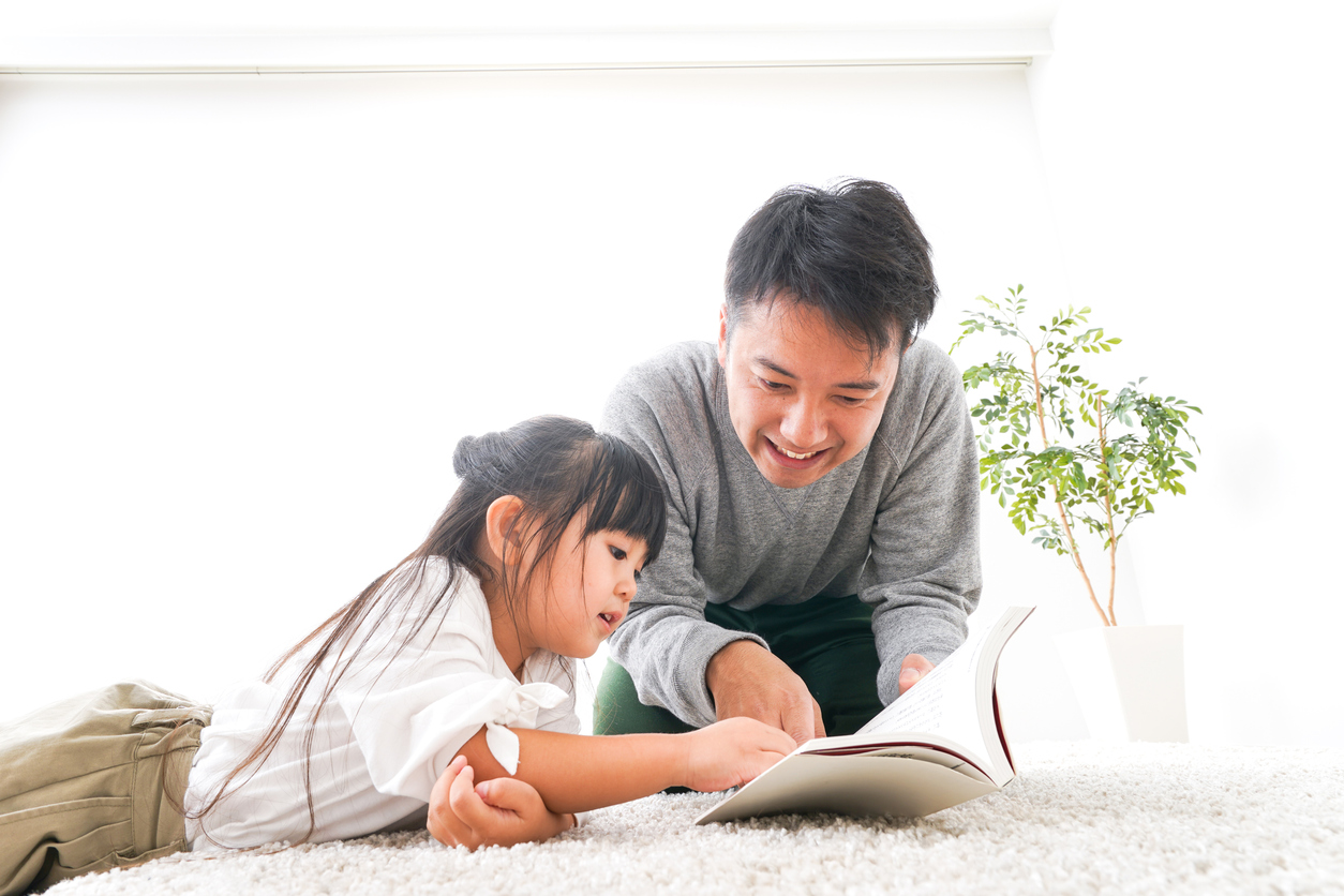 Father reading a book to his child