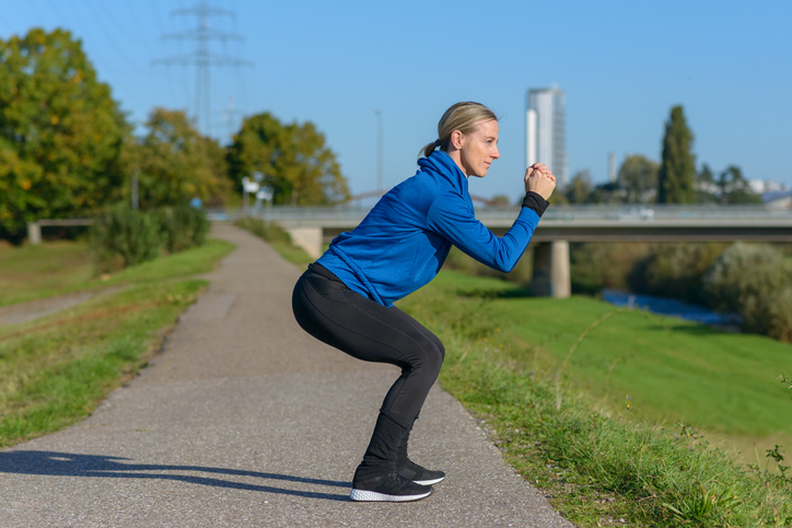Fit woman doing crouch stretches to warm up